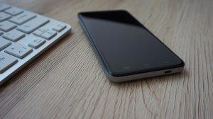 Smartphone en clavier Apple disposés sur un bureau en bois